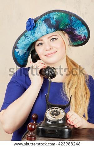 Blonde in wide-brimmed blue ladies hat talks by retro phone at studio.