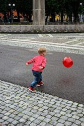 blonde kid wearing red stripes and sneakers running after red ball on cobblestone street