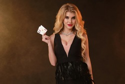 Blonde lady in black dress with feathers and necklace. She is smiling, showing two aces, posing on black smoky background. Poker, casino. Close-up