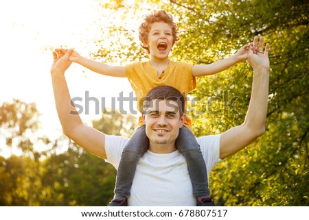 Blonde laughing kid riding on father shoulders holding hands in park.