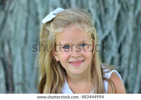 Stock Photo Blonde little girl is smiling at the camera.