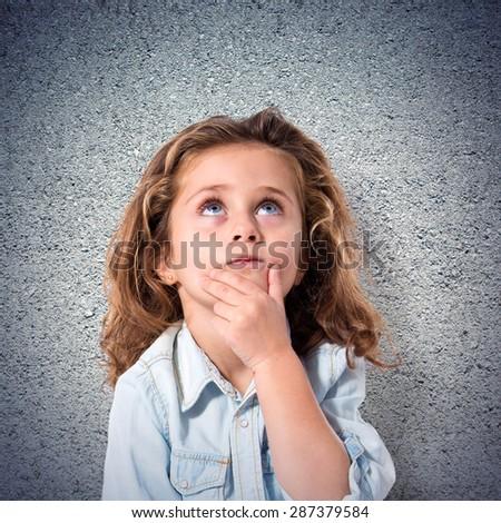 Blonde little girl thinking over textured background