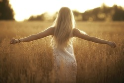 blonde long hair nature summer / happy adult girl with developing in the wind long blonde hair in the summer field