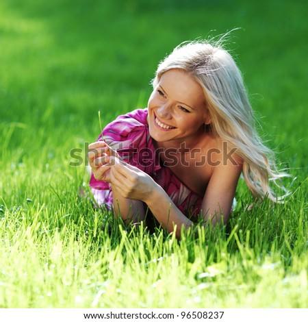 blonde lying on green grass