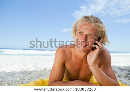 Blonde man lying on his beach towel while talking on his mobile phone