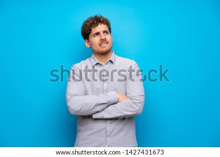 Blonde man over blue wall with confuse face expression