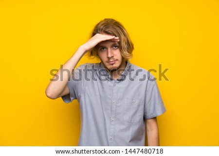 Blonde man over isolated yellow background looking far away with hand to look something