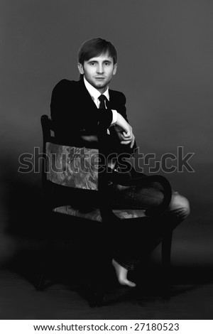 blonde man sitting on old chair turned back looking forward,wearing  jeans,white shirt,black tie,jacket,with hands free pose appear and legs free isolated