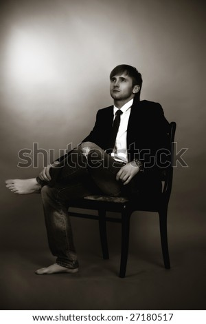 blonde man sitting on old chair turned right looking up,wearing jeans,white shirt,black tie,jacket,with legs crossed appear and hands on free pose isolated