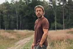 Blonde man with a stubble beard in a brown t-shirt on a sandy path in a field near a pine forest in summer. Front view.