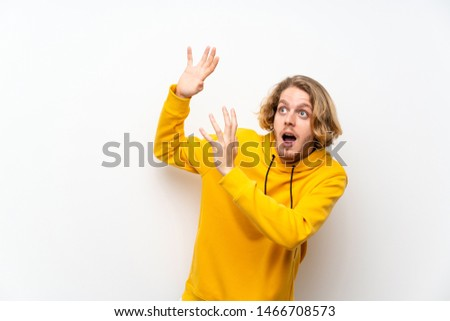 Blonde man with  sweatshirt over white wall nervous and scared #1466708573