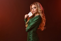 Blonde model in green dress and jewelry. Looking at you, showing two playing cards, posing sideways on brown background. Poker, casino. Close-up