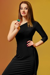 Blonde model with bright make-up, in black dress is showing one green chip, posing against colorful background. Gambling, poker, casino. Close-up.