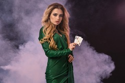 Blonde model with make-up, in green dress and jewelry. Put hand on hip, showing two aces, posing on black smoky background. Poker, casino. Close-up