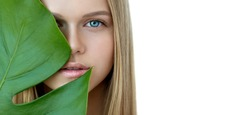 Blonde model with natural make up and green leaf isolated on white. Spa and wellness. Youth, teens and skin care concept.  Close up, selective focus, copyspace.
