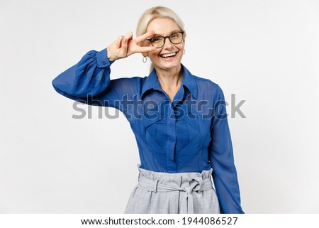 Blonde optmistic successful employee business woman 40s in blue classic shirt glasses formal clothes ure showing victory vsign gest isolated on white background studio portrait Achievement concept. Zdjęcia stock ©
