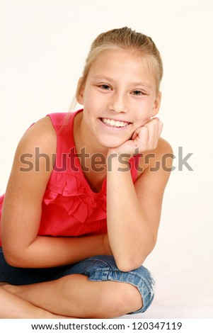 blonde preteen girl isolated on white seated on floor