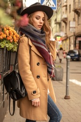 Blonde pretty woman on a walk in european old city center. Cold autumn weather. Girl wears brown coat, plaid scarf and stylish hat