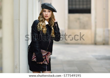 8a4bc5826b3 Blonde russian woman in urban background. Beautiful young girl wearing beret
