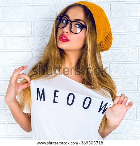 Blonde sexy girl posing near brick wall, happy mood, sensual beauty face, funny shirt, hipster glasses and hat.