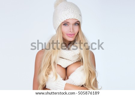 Blonde sexy woman in fashionable winter cap, scarf, gloves. Studio photo.