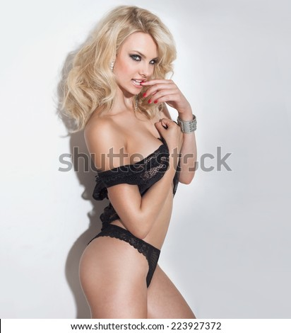 Blonde sexy woman posing over white background in black lingerie, looking at camera.