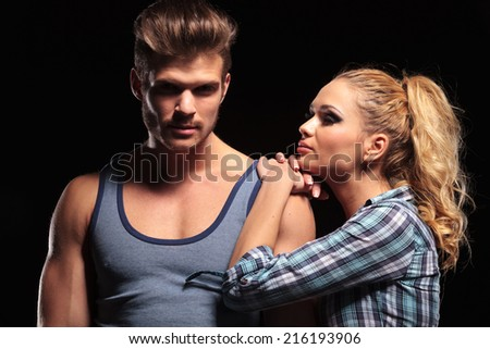 Blonde sexy woman resting her hands and chin on her boyfriend shoulder. The man is looking at the camera.
