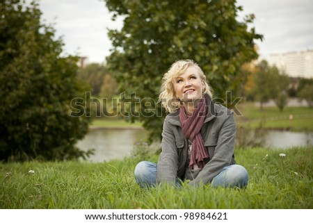 Blonde sits on the grass and looking up into the sky