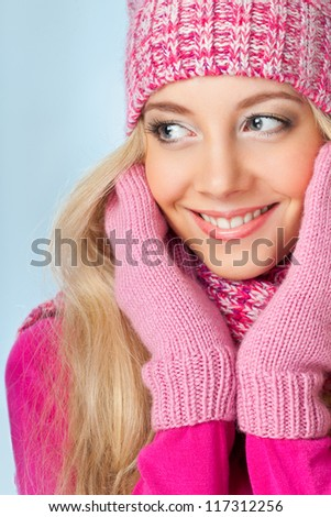 blonde smiling woman wearing pink knitwear over blue background