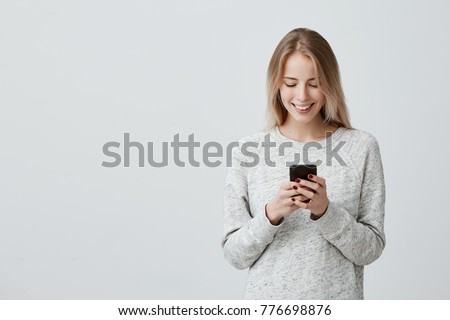 Blonde smiling young woman demonstrating white teeth using cell phone, messaging, being happy to text with her boyfriend, looking at screen of smartphone. Modern technologies and communication #776698876