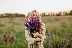 Blonde smiling young woman holding a lupine bouquet on nature background. The concept of beauty and romance. Sunset light.