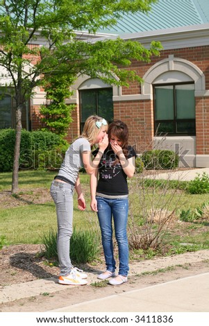 blonde teen girl whispering to brunette teen girl