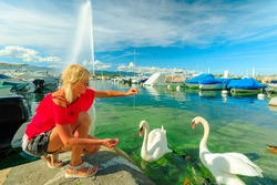 Blonde tourist girl feeding white swans in turquoise waters of Geneva Lake in Geneva Harbor with 140m high fountain called Jet d'Eau. Marina with boats, sailboats and yachts. French Swiss, Switzerland