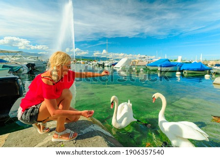 Blonde tourist girl feeding white swans in turquoise waters of Geneva Lake in Geneva Harbor with 140m high fountain called Jet d'Eau. Marina with boats, sailboats and yachts. French Swiss, Switzerland Foto stock ©
