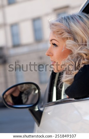blonde tourist watches something from her car, she\'s blonde and beautiful and she may have spotted something amazing