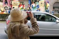 Blonde tourist wearing a colonial hat during the carnival. Girl photographs the carnival floats in Verona during a parade.
