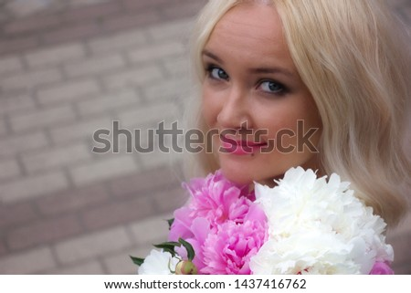 Blonde with a bouquet of flowers posing against the background of a stone wall. Portrait of a young girl with white hair closeup. #1437416762