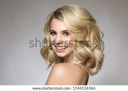 Blonde with curls on a gray background, natural make-up and clean skin. beautiful smile and big eyes. Portrait woman #1144136366