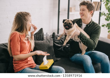 blonde woman allergic to dog sneezing and looking at cheerful man holding cute pug