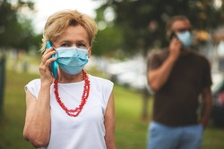 Blonde Woman and her son Wearing a Mask. Social distancing. Senior woman and young man with cell phone, during Covid-19 pandemic, outdoor.
