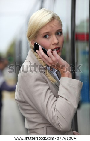 blonde woman at phone having an anxious face expression