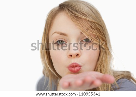 Blonde woman blowing on her palm against a white background - stock photo