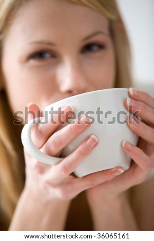 Blonde woman drinking from a white mug and looking at the camera
