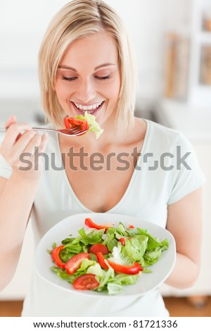 Blonde woman eating salad in the kitchen