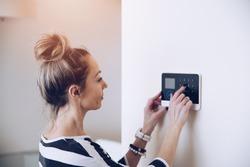Blonde woman entering code on home security alarm keypad. Alarm code.