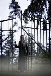 Blonde woman entering the gate of an cemetery