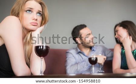 Blonde woman feeling jealous of couple flirting beside her in a bar
