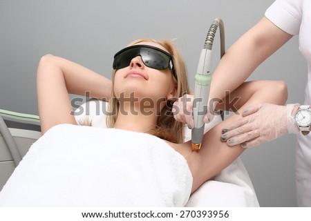 Blonde woman having underarm Laser hair removal epilation. Laser treatment in cosmetic salon