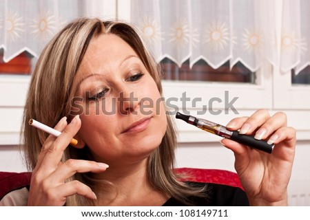 Blonde woman holding a normal cigarette and electrical and chooses between them