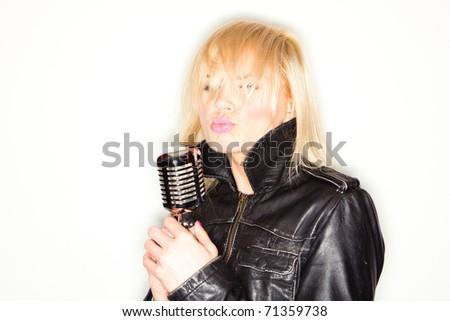 blonde woman holding a retro microphone wearing black jacket , singing rockstar